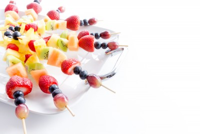 Serving of colorful healthy tropical fresh fruit kebabs with an assortment of exotic fruit on a white platter for a tasty vegan or vegetarian buffet over white with copy space