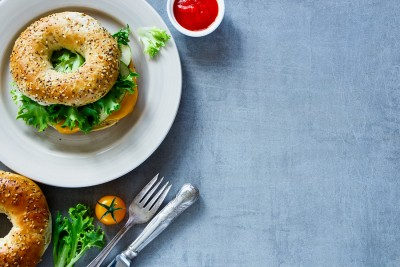 Tasty cheese sandwich on bagel with fresh vegetables over grey vintage background border top view copy space. Vegetarian and healthy eating concept. ** Note: Visible grain at 100%, best at smaller sizes