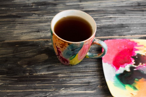 Colorful cup of tea on a wooden table in rustic style reflecting Holi